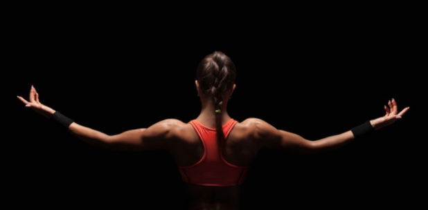 a woman showing off her back muscles on a black background