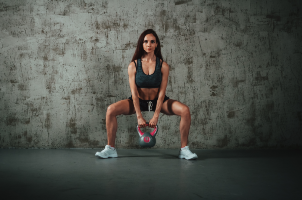 a woman doing a squat with a kettle bell